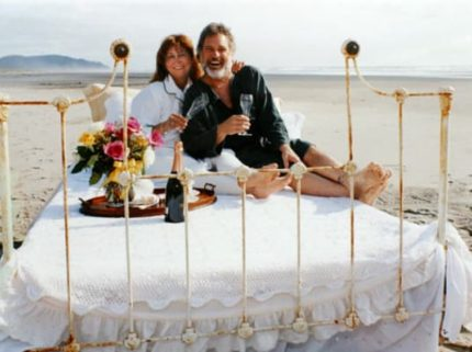 man and lady in robes drinking champagne on bed on beach
