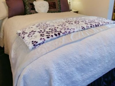 Garden Suite bed with white bedspread and purple accents