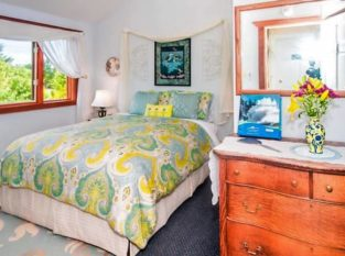 Pacifica Suite bedroom with antique dresser and bed with yellow and blue comforter