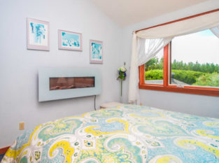 Pacifica Suite with yellow and blue bedspread and wall fireplace