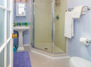 Bathroom of Hideaway Suite with pedestal sink and corner shower
