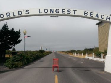 Red chair sitting under World's Longest Beach sign across road