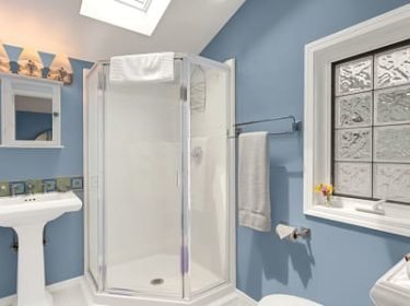 Hideaway Suite bathroom with blue walls, pedestal sink, corner shower