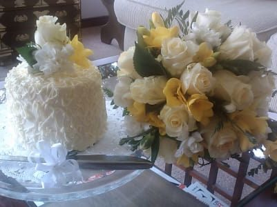 wedding cake with bouquet of yellow and white flowers