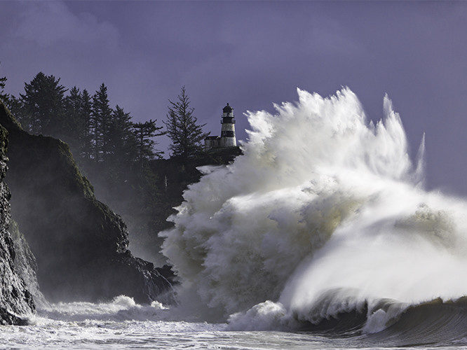 lighthouse with water hitting rocks and splashing high into air