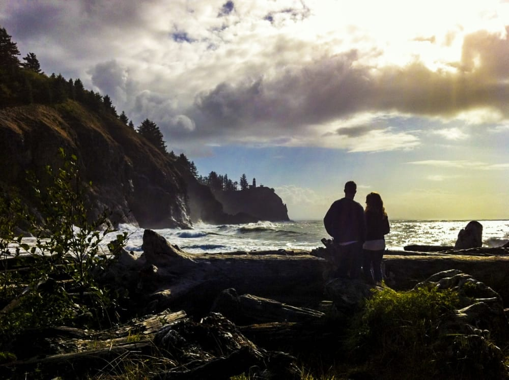 couple standing on shore at dusk